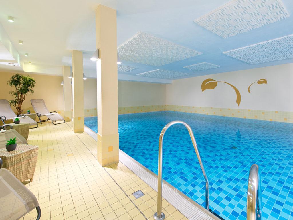 Das hauseigene Schwimmbad im Hotel mit Liegen und Tischen am Rand