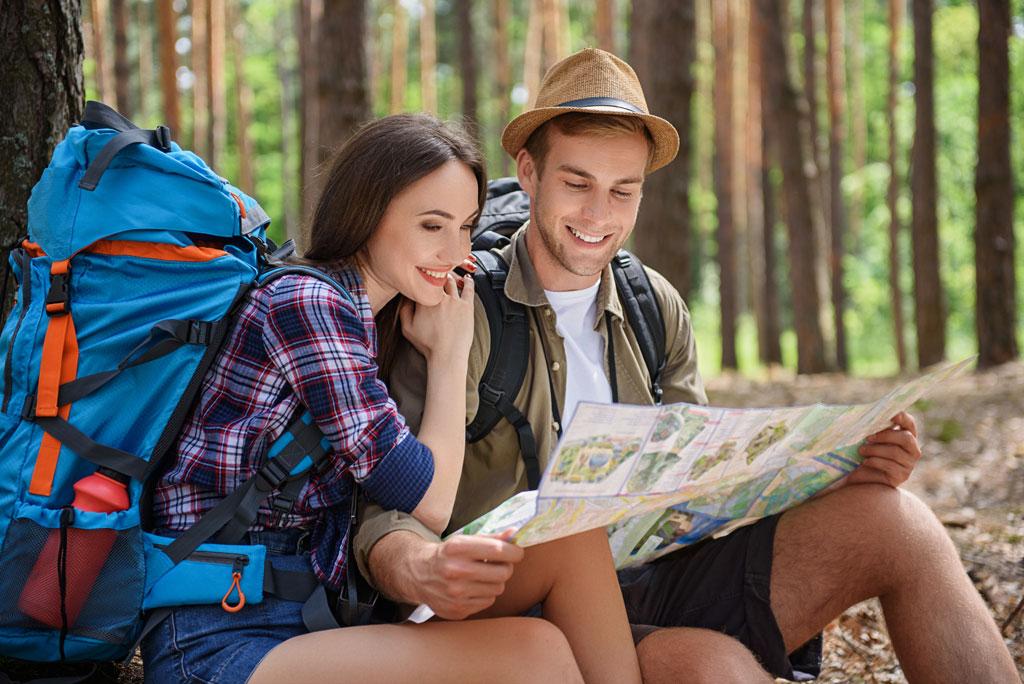 Junge Frau mit großem Wanderrucksack und junger Mann mit Hut sitzen im Wald und gucken in die Karte