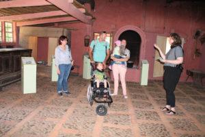 Drei Frauen und ein Mann stehen gemeinsam mit einem Kind im Rollstuhl in einem alten Bauernhaus und unterhalten sich