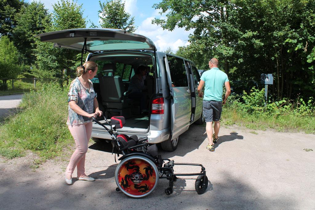 Eine Frau und ein Mann laden einen Rollstuhl aus einem grauen Kleinbus, der auf einem Behiundertenparkplatz steht