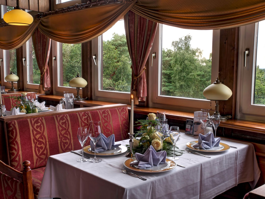 Einladend gedeckter Tisch mit brennender Kerze und Blick aus den Fenstern über die Wälder
