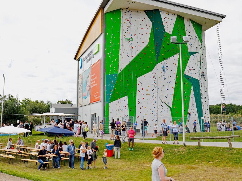 Besucher vor dem hohen Gebäude mit einer großen Kletterwand