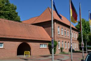 Großes altes Rathaus in Buchholz aus roten Mauersteinen und roten Dachziegeln mit Flaggen im Vordergrund