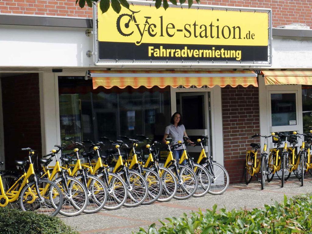 Fasade und Eingang der Cycle Station mit vielen gelben Leihfahrrädern