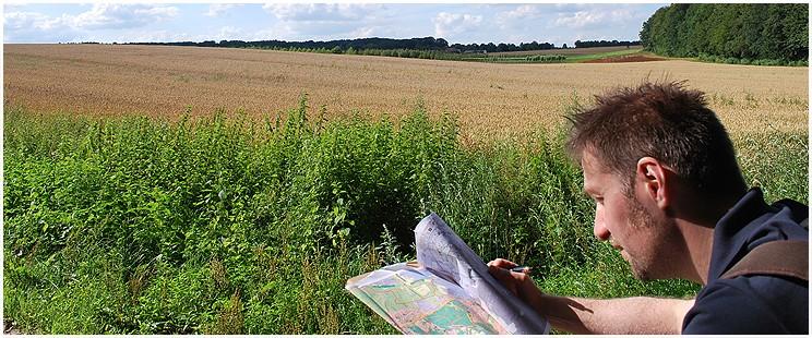 Mann guckt in eine Karte am Rande eines Feldes mit Wäldern im Hintergrund