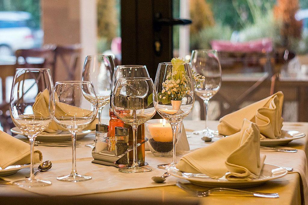 Einladend gedeckter Tisch mit Weingläsern. Öffnet Seite: Essen und Trinken