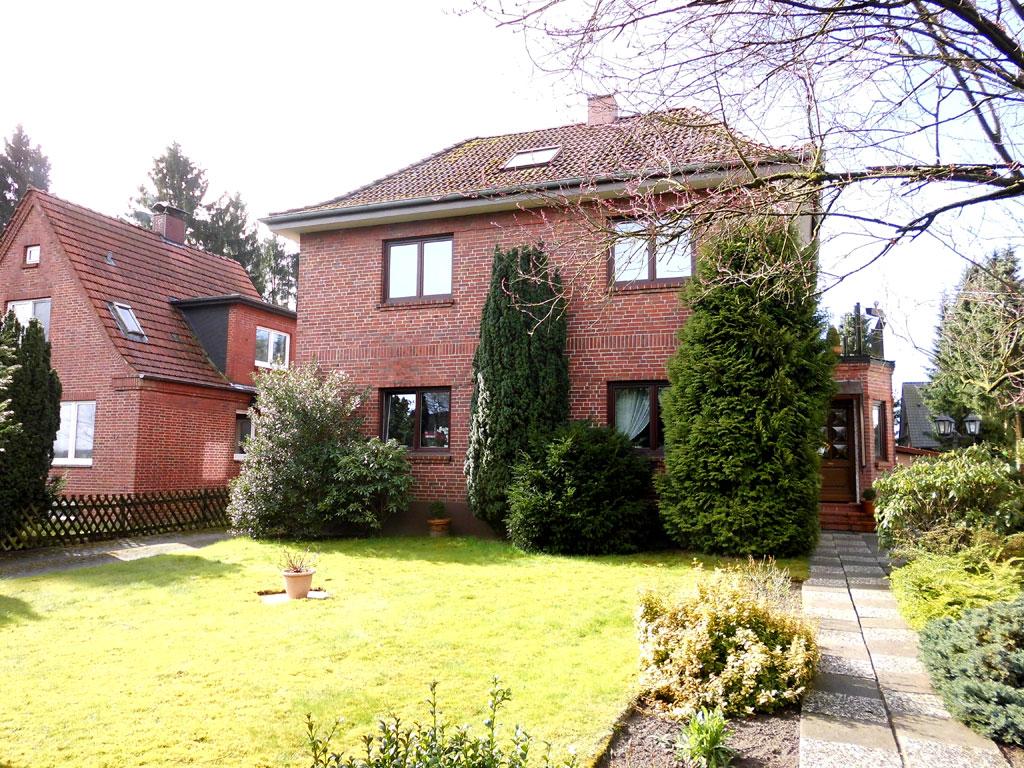 Zweifamilienhaus aus roten Backsteinen über zwei Etagen mit grünem Rasen und ein paar Bäumen