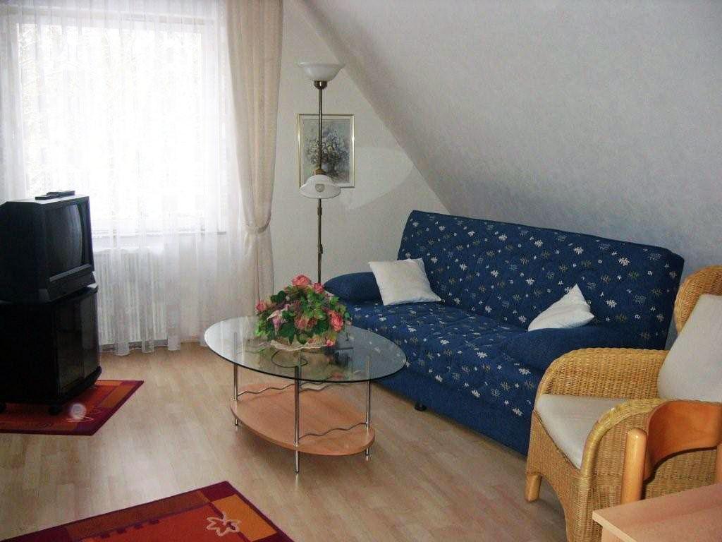 Wohnzimmer mit einem blauen Sofa unter der Dachschrägen und einem Fernseher neben einem großen Fenster