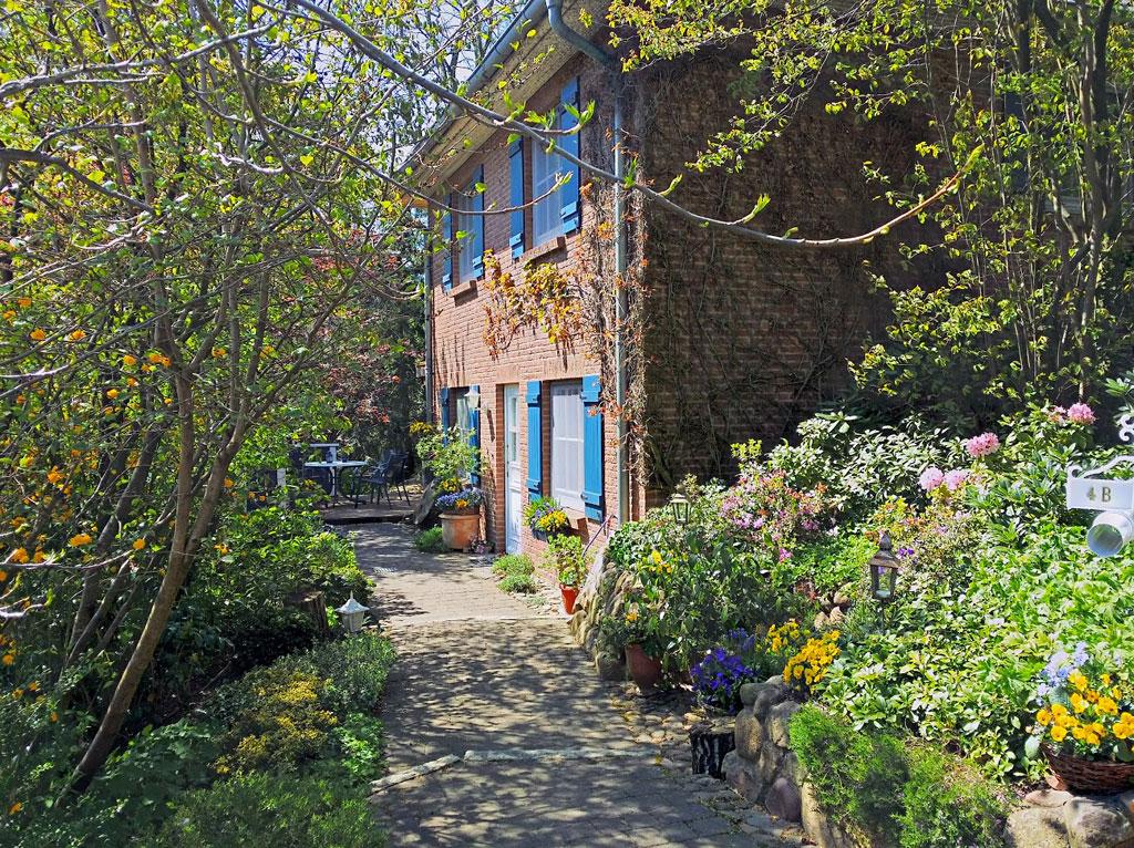 Zwei Etagen Haus aus rotem Backsteinen mit blauen Fensterläden und sehr vielen Pflanzen und Büschen davor