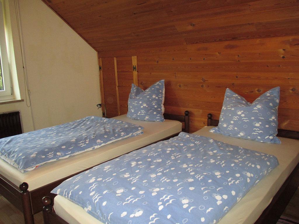 Schlafzimmer mit zwei Einzelbetten vor einer mit Holz vertäfelten Wand und Dachschrägen