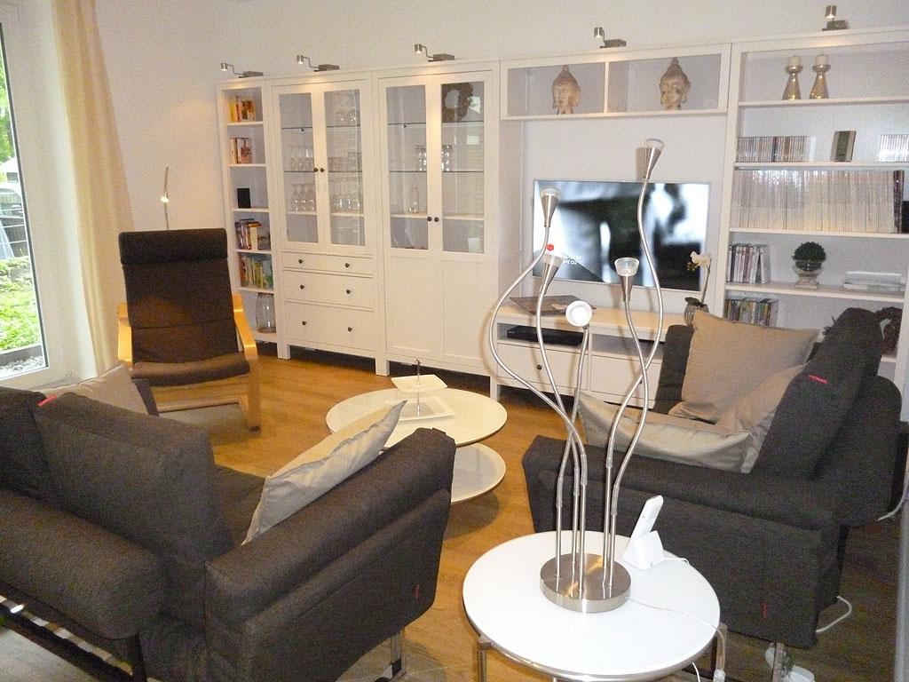Modern eingerichtetes Wohnzimmer mit weißen Schränken, Flachbildfernseher und grauen Sofas