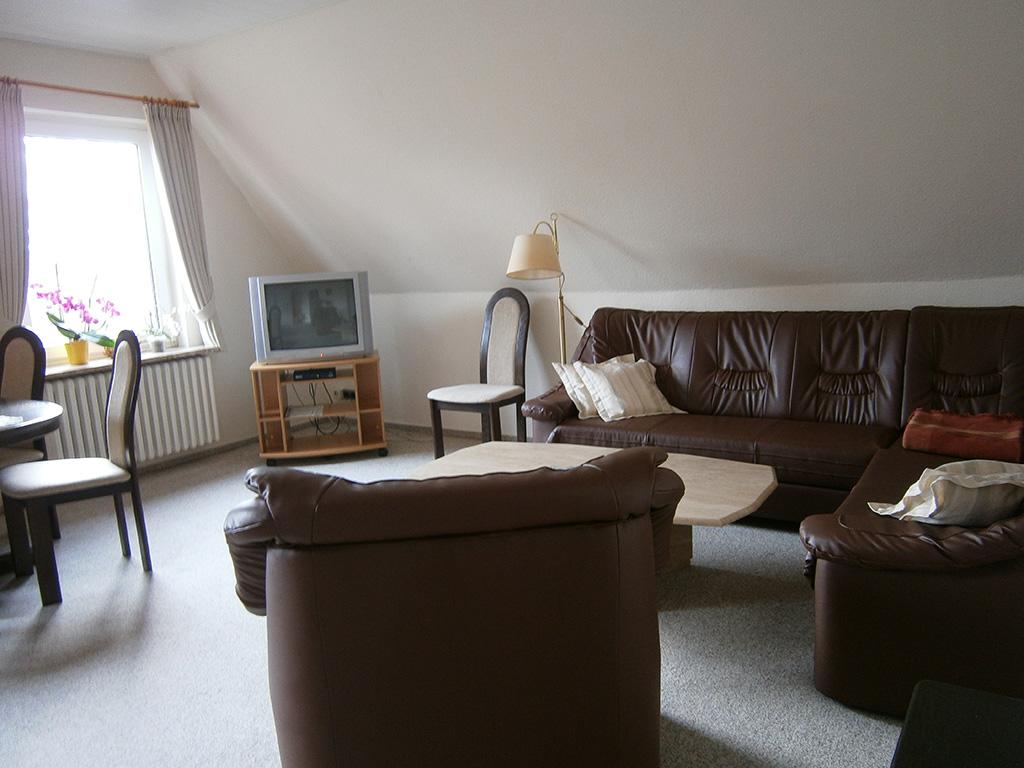 Geräumiges großes Wohnzimmer mit großem braunen Ledersofa und Fernseher in der Ecke