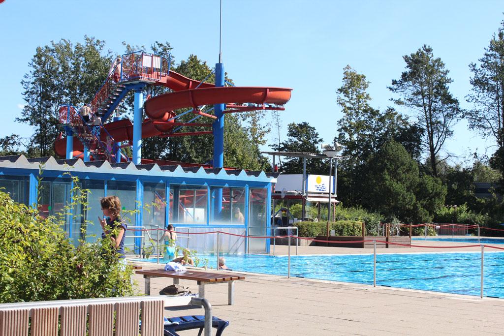 Blaues Wasser im Schwimmbecken mit einer großen roten Rutsche im Hintergrund