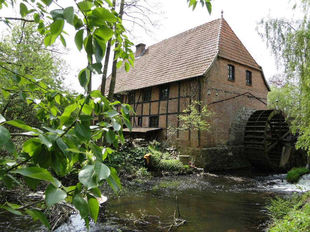 Altes Fachwerkgebäude mit großem Wasserrad im Fluß