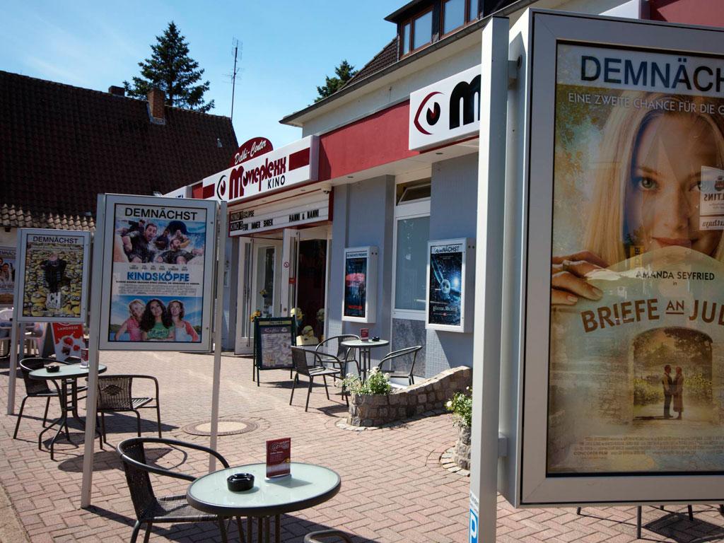 Der Eingangsbereich mit Terrasse davor. Auf der Terrasse stehen Stühle und Tische zwischen Plakaten mit Kinofilmankündigungen.