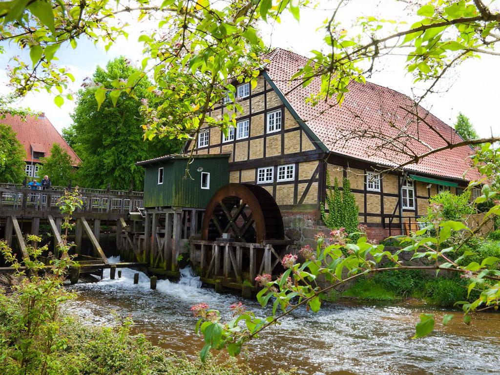 Altes Fachwerkgebäude mit dem großen Mühlenrad an der Este