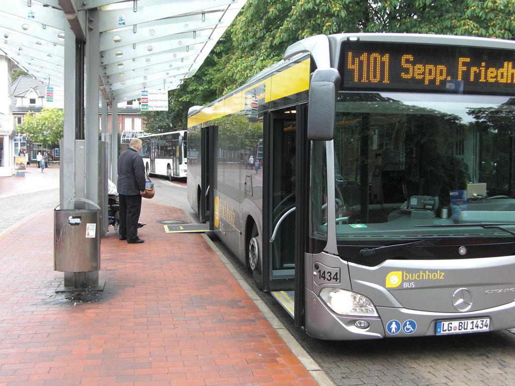 Ein Niederflurbus hält an einer Haltestelle mit ausgeklappter Rampe für Rollstuhlfahrer