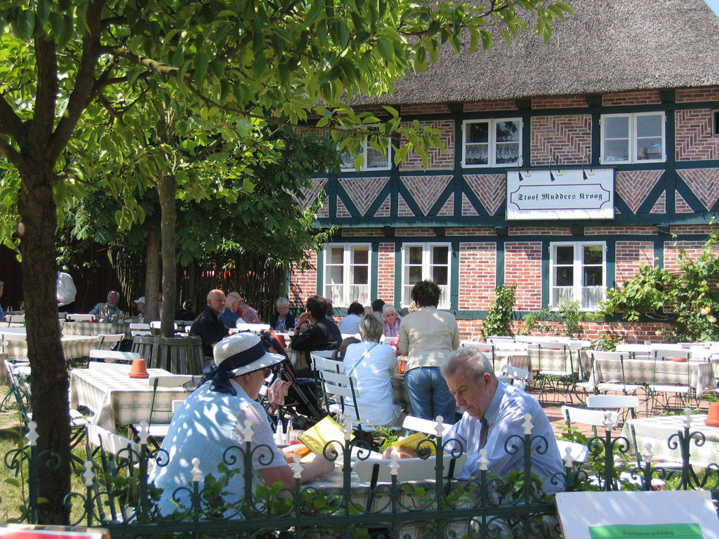 Besucher auf der Terrasse mit zahlreichen Tischen und Stühlen zwischen kleineren grünen Bäumen und ein Fachwerkhaus mit Reetdach im Hintergrund