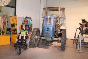 Ein Mann steht mit einem lachenden Kind im Rollstuhl neben einem großen blauen Traktor in einer Halle