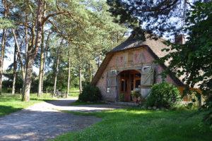 Schönes altes Fachwerkgebäude mit Reetdach und geöffnetem Dielentor