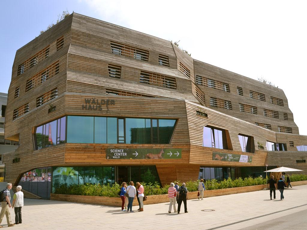Die Fassade aus Holz und Glas von dem futuristische Wälderhaus mit spazierenden Personmen davor