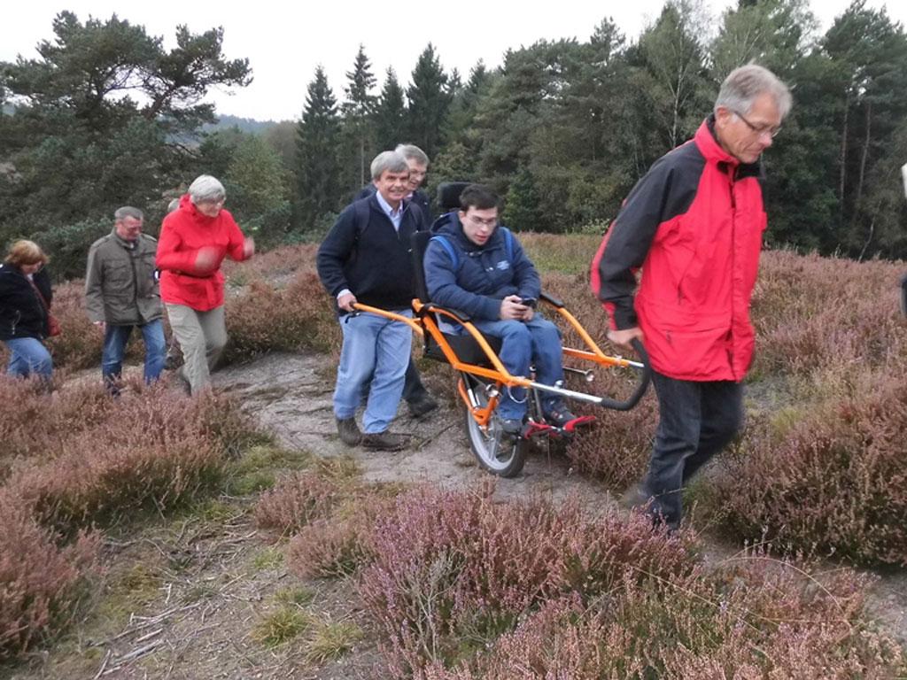 Eine Gruppe Menschen geht gemeinsam mit einem Rollstuhlfahrer im Wanderrollstuhl Joelette über einen schlecht begehbaren Weg durch die Heide