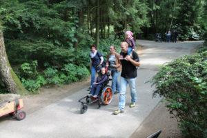 Zwei Frauen, ein Mann mit Kind auf den Schultern und ein Kind im Rollstuhl auf einem asphaltierten Weg durch einen grünen Wald