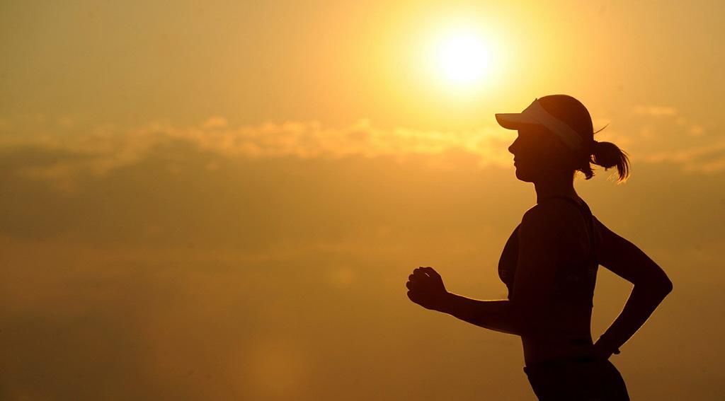 Frau läuft vor Sonnenuntergang