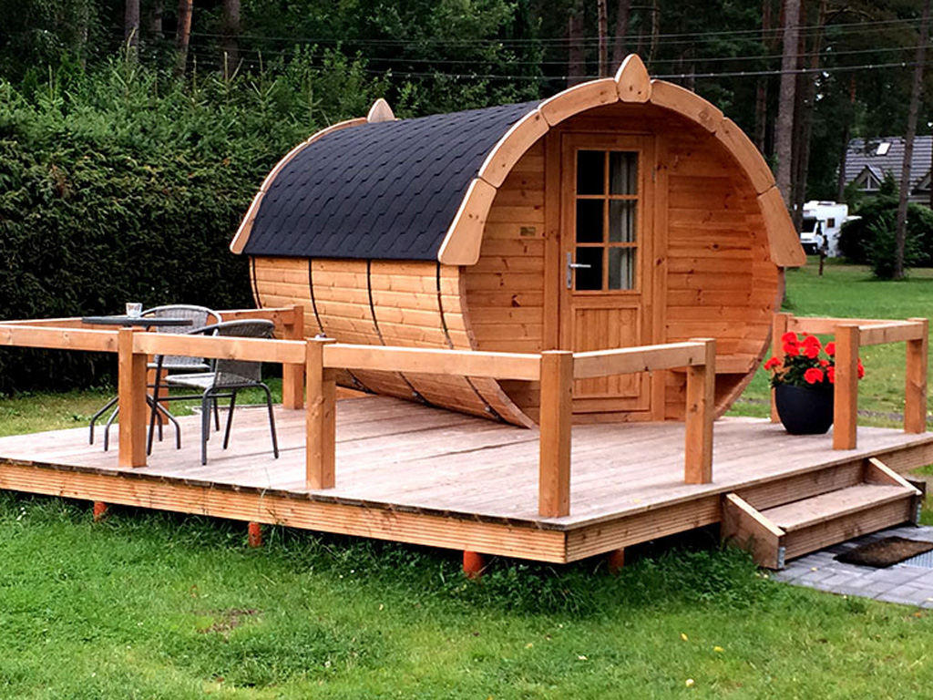 Ein kleines Ferienhaus aus Holz in Form eines Fasses mit Terrasse aus Holz und zwei Stühlen mit Tisch