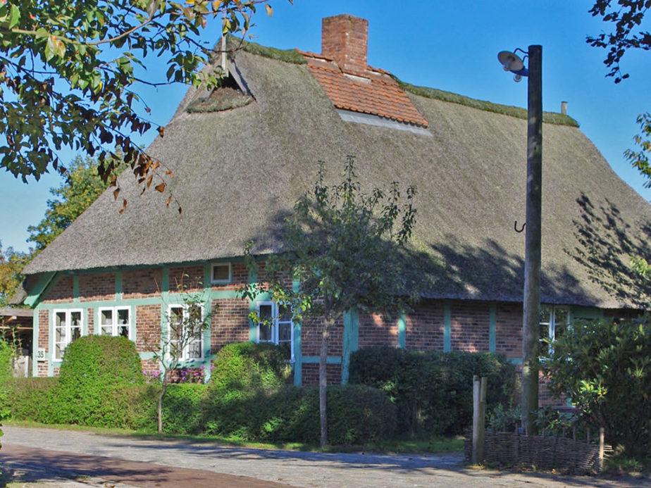 Fachwerkhaus aus roten Backsteinen mit Reetdach