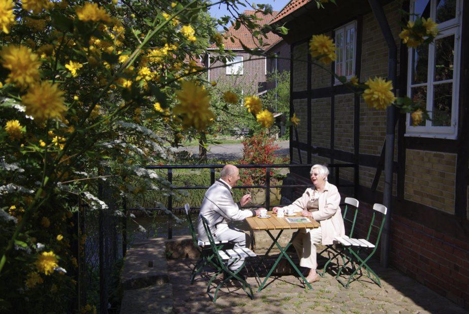 Eine Dame und ein Herr sitzen auf der Terasse vor der Mühle und trinken Café