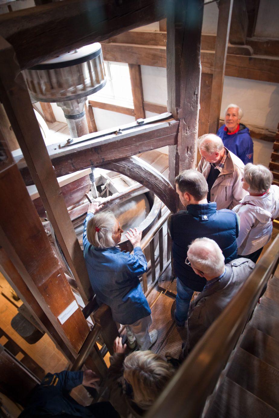 Besucher bestaunen das Mahlwerk in der Mühle