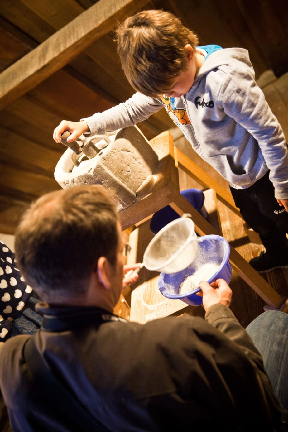Ein Mann und ein Kind mahlen Mehl mit einem Mahlstein