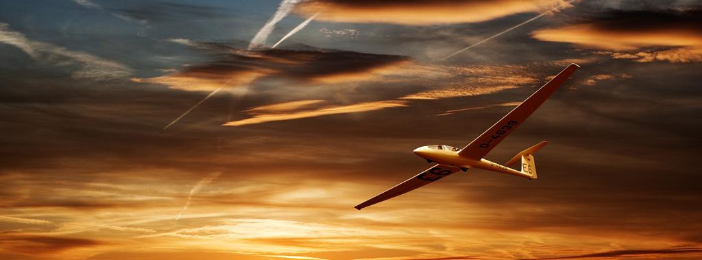 Ein Segelflugzeug fliegt unter leichten Wolken durch den roten Himmel