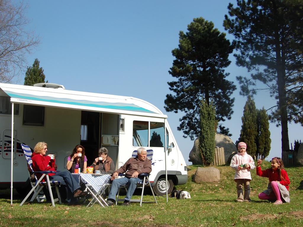 Eine Familie sitzt vor einem Wohnmobil und trinkt Café und 2 Kinder spielen auf dem Rasen