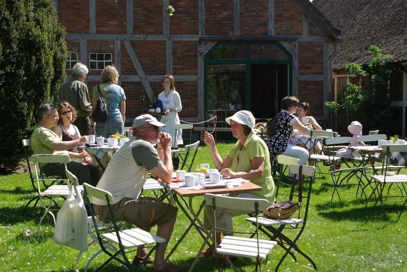 Tische und Stühle im Garten vor einem Fachwerkgebäude