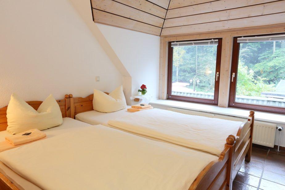 Helles, gemütliches Doppelzimmer mit Doppelbett vor einem Fenster mit schönen Ausblick