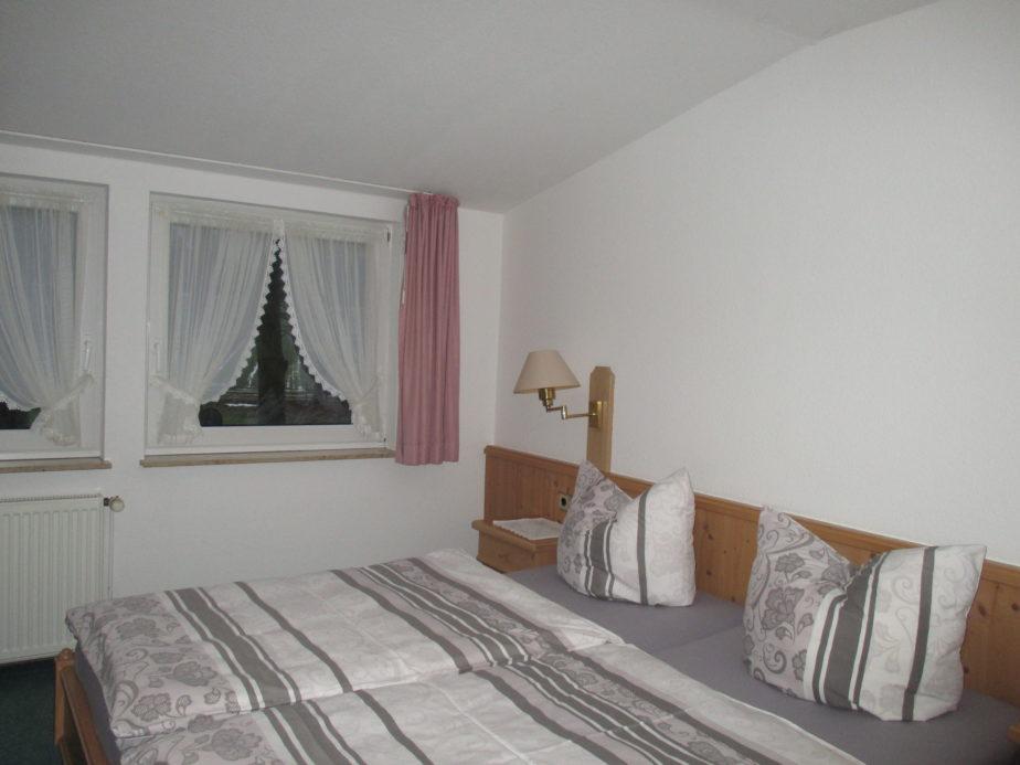 Großes Doppelbett mit Nachttisch und Leselampe und im Hintergrund 2 große Fenster