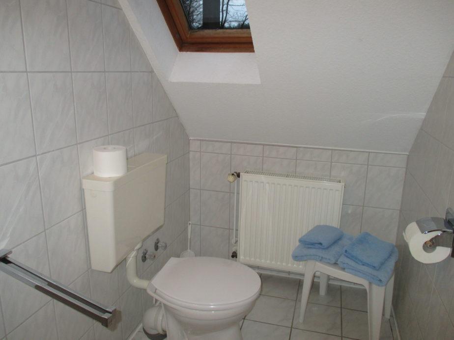 Kleines Badezimmer mit WC und kleinen Hocker mit Handtüchern