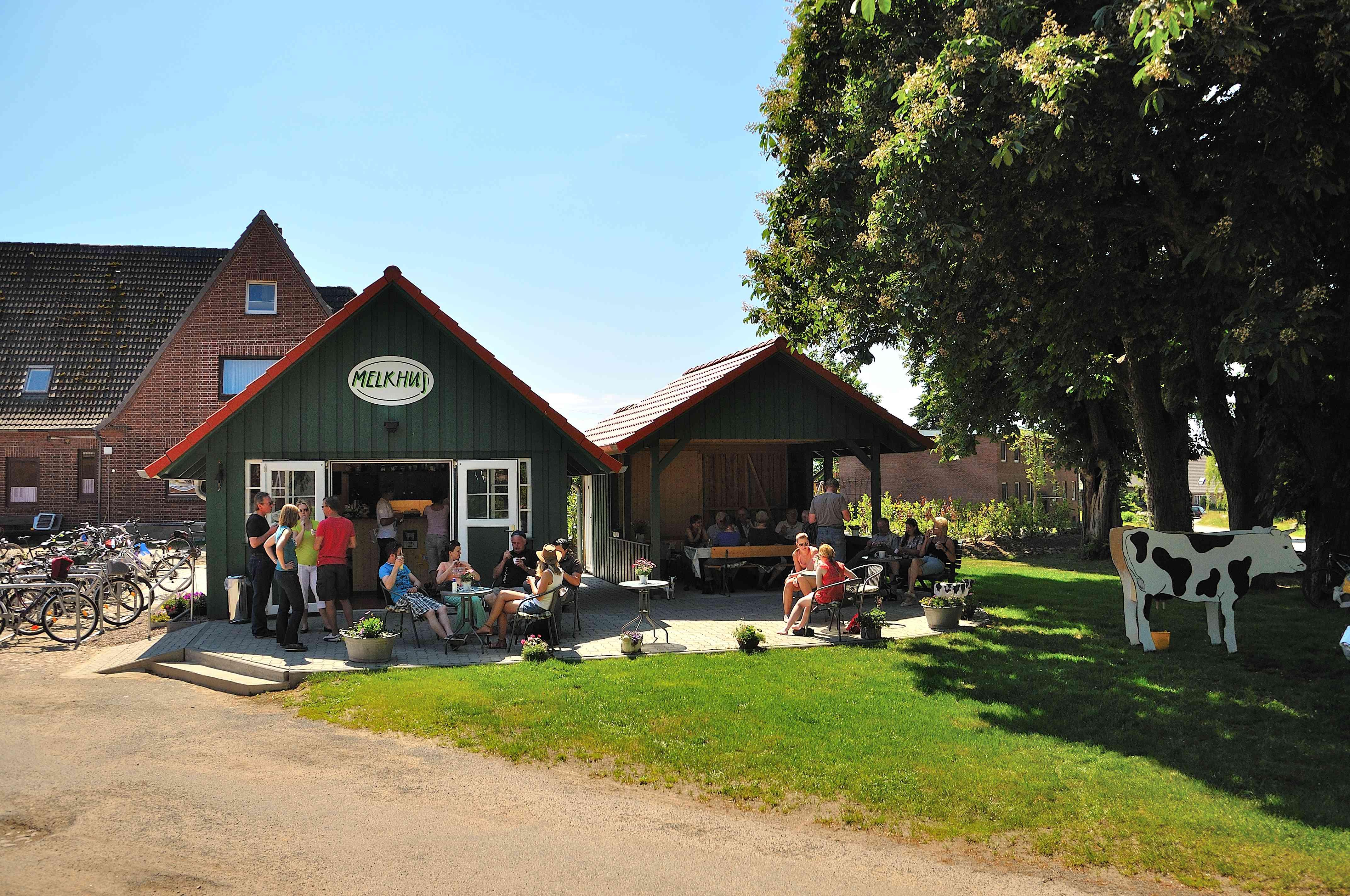 Besucher auf dem Bauernhof stehen vor dem kleinen grün-weißen Melkhus-Anbau mit rotem Pfannendach