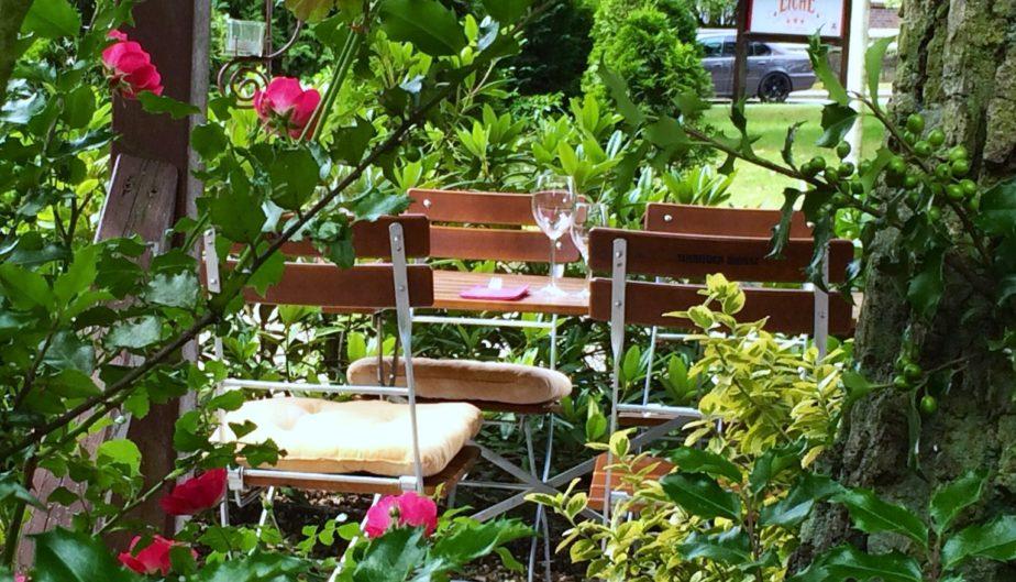 Ein Tisch und 4 Stühle auf einer Terrasse im Grünen