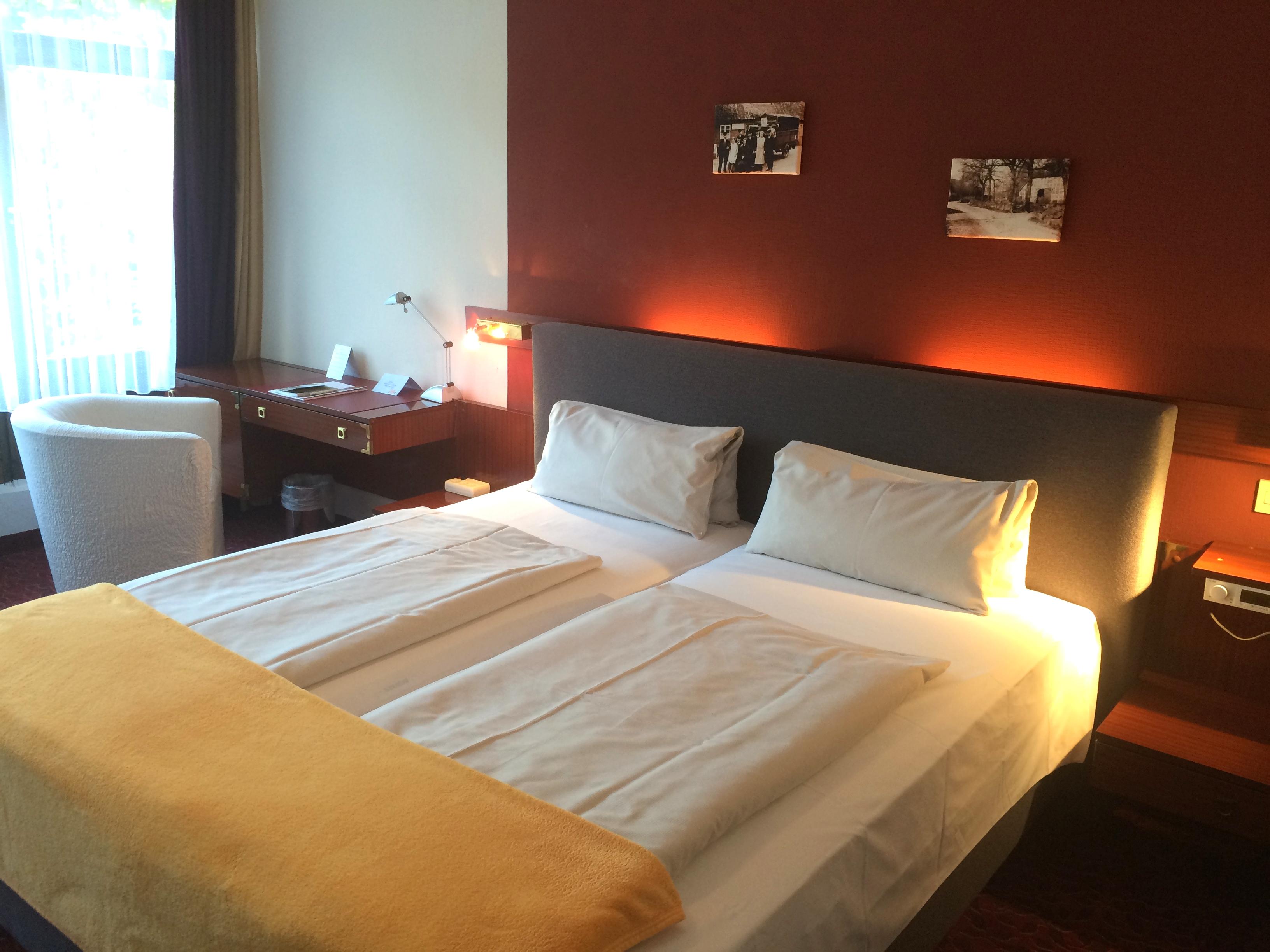 Großes Doppelbett vor einer roten Wand