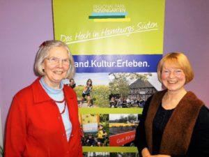 2 Gästeführerinnen vor dem Logo des Regionalparks Rosengarten