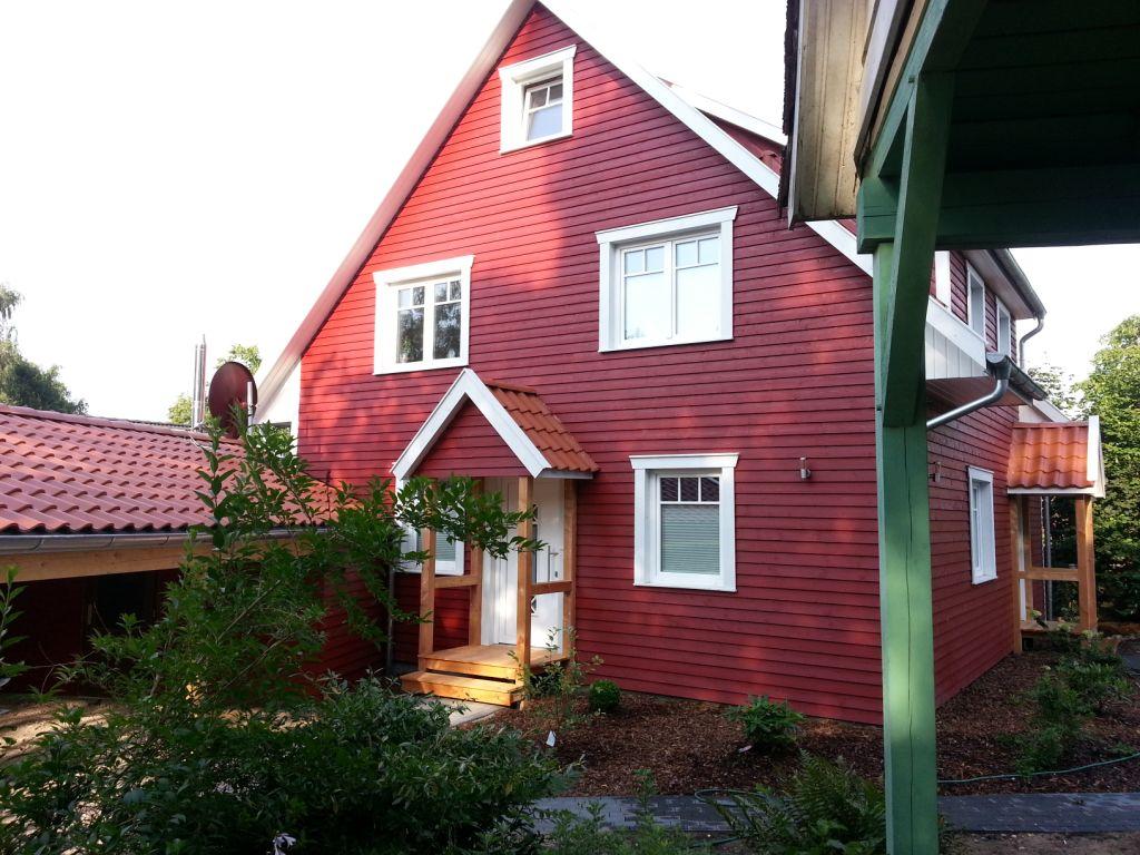 Rotes Schwedenhaus mit einem überdachten Eingangsbereich