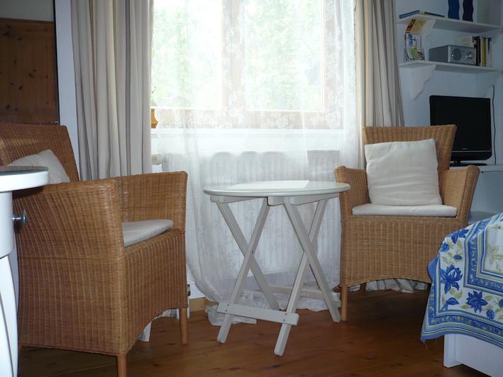 12 qm Gästezimmer ausgestattet mit einem kleinen Tisch und 2 Korbsessel sowie Doppelbett