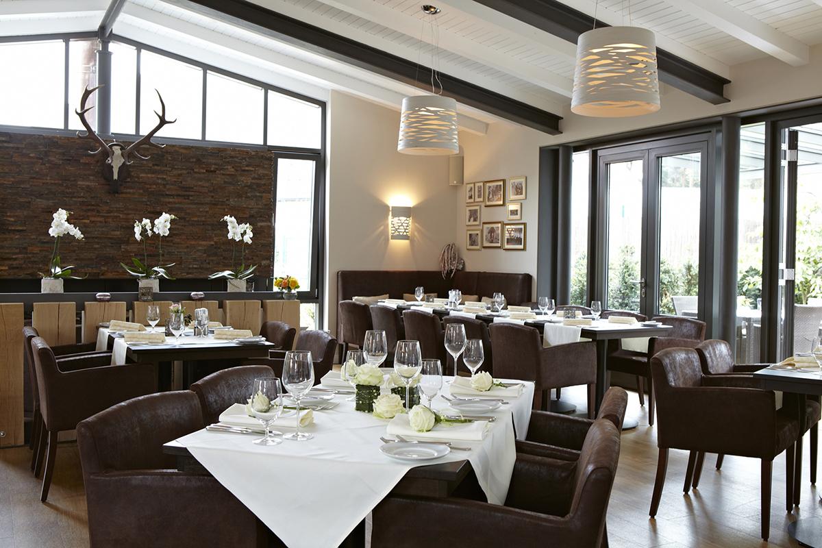 Modern und stilvoll gestalteter Gastraum in weiß und brau gehalten.