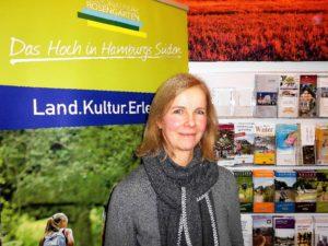 Dagmar Bellut , zertifizierte Gästeführerin vor dem Logo des Regionalparks Rosengarten