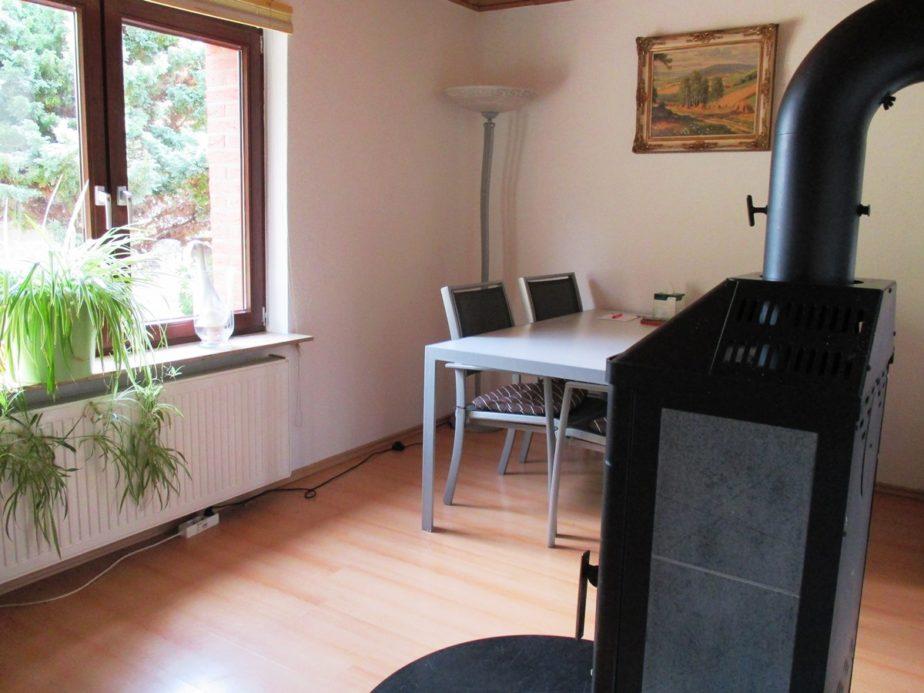 Wohn- und Esszimmer mit Tisch und 4 Stühlen und Kaminofen im Erdgeschoss
