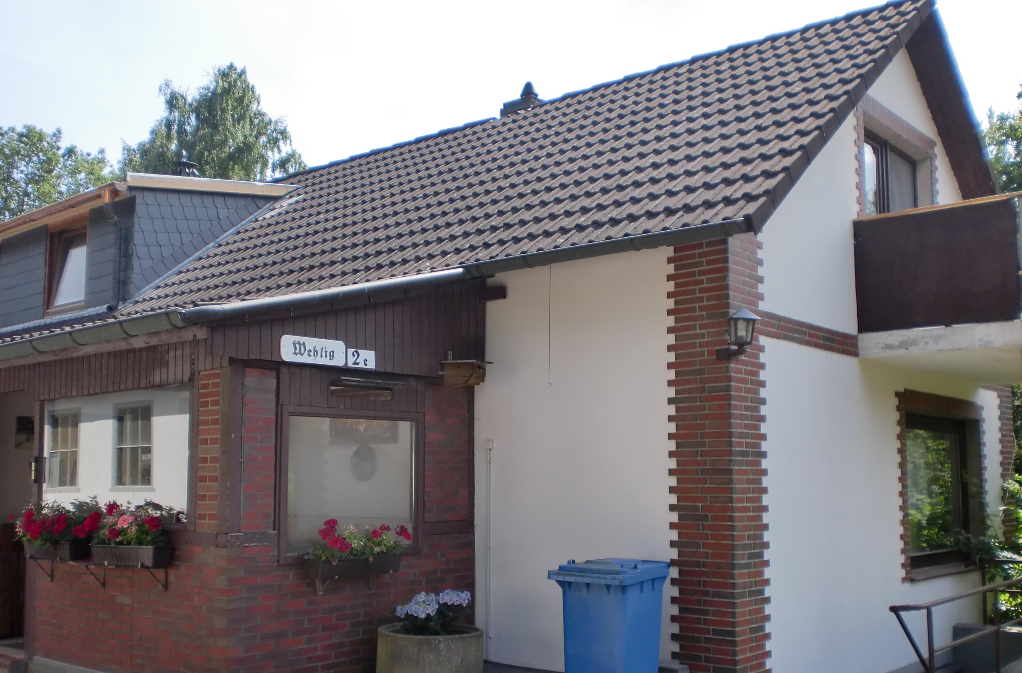 Aussenansicht Einfamilienhaus mit kleinem Anbau und Blumenkästen an Fenstern